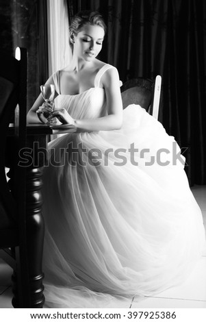 Beautiful blonde bride seats near table, is ready for a new bright life, inside interior. White Wedding dress. Pretty young woman love. Black and white photo.