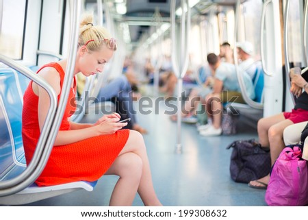 Beautiful blonde caucasian lady in red dress traveling by metro. - stock photo