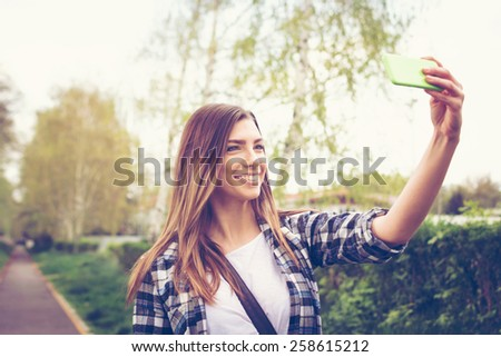 Beautiful blonde Caucasian teenage girl taking a selfie with smartphone in park in spring. Cute happy young woman photographing herself. Horizontal, retouched, filter, copy space. - stock photo