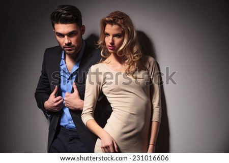 Beautiful blonde fashion woman posing near a grey wall while her boyfriend is fixing his jacket.