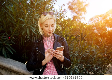 Beautiful blonde female dressed in fashionable clothes watching video on her mobile phone while relaxing outdoors in sunny day, young charming woman using cell telephone while standing in green park - stock photo