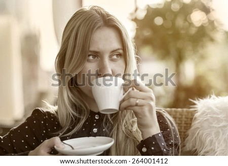 Beautiful blonde female drink coffee in cafe - stock photo