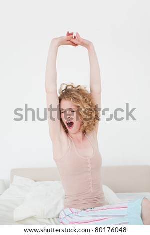 Beautiful blonde female stretching in her bedroom in her apartment - stock photo