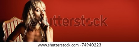 Beautiful blonde gesturing silence on red background (banner) - stock photo