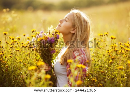 Beautiful blonde girl among the wildflowers in summer - stock photo