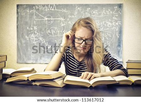 Beautiful blonde girl concentrated while studying at school - stock photo