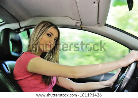 Beautiful blonde girl driving a car - stock photo