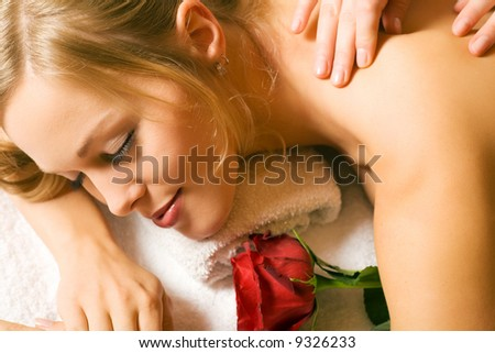 Beautiful blonde girl getting a massage and feeling visibly good about it - stock photo