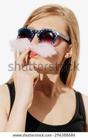 Beautiful blonde girl having fun and making mustache from pink cotton candy. Wearing sunglasses. White background, not isolated. - stock photo