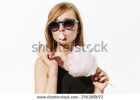 Beautiful blonde girl having fun and posing pink cotton candy. Wearing sunglasses with stars. White background, not isolated. - stock photo
