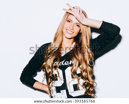 Beautiful blonde girl hipster smiles and showing sign of victory putting her hand to her forehead on white background. Close up. Indoor. Warm color. Hipster. - stock photo