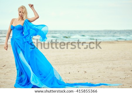 Beautiful blonde girl in a blue dress against the sea