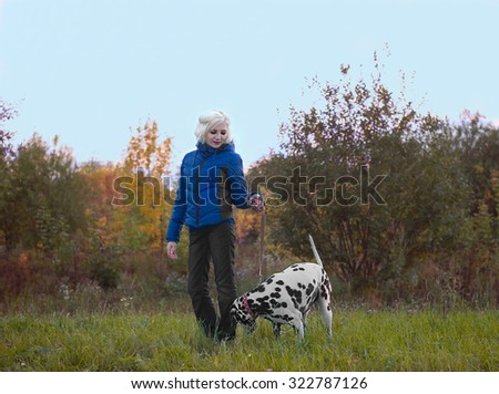 Beautiful blonde girl in a blue jacket and black jeans walking with a dog breed Dalmatian on nature autumn evening, the dog sniffs the grass