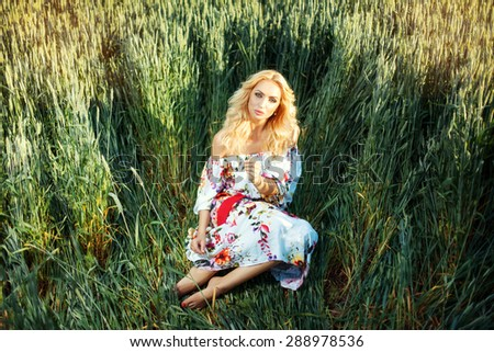 Beautiful blonde girl in a light summer dress. She is sitting on the grass in the field.  - stock photo