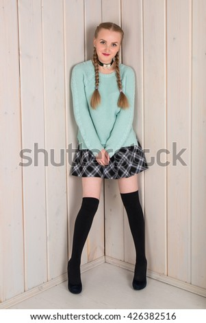 Beautiful blonde girl in a short skirt and stockings. Studio portrait against a background of a wooden wall. The blonde with pigtails in the image of schoolgirl. - stock photo