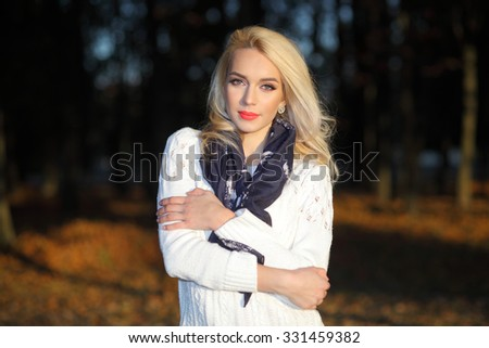 beautiful blonde girl in a white sweater freezing in the autumn park - stock photo