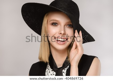 Beautiful blonde girl in black hat keeps hand near the face laughs and smiles on the gray background. Concept of the beauty. - stock photo