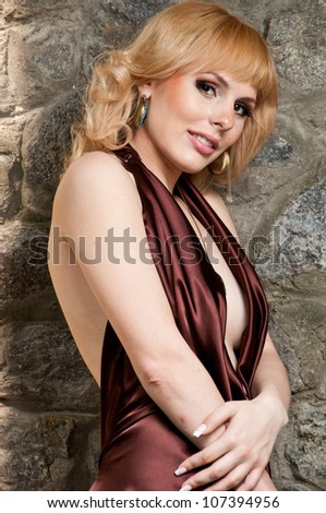 Beautiful blonde girl in evening dress, posing against a stone wall
