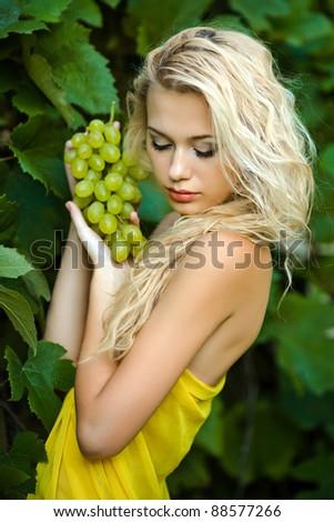 beautiful blonde girl in green grape - stock photo