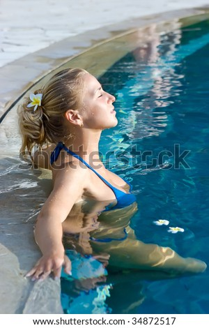 Beautiful blonde girl in hotel swimming pool with flower in long hair