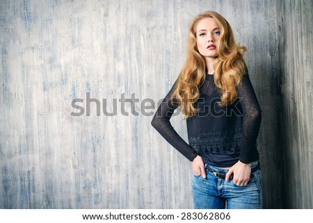 Beautiful blonde girl in jeans clothes posing by the grunge wall. Fashion. - stock photo