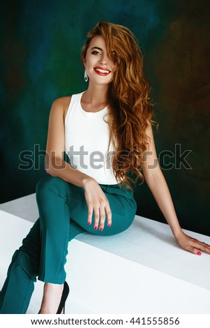 Beautiful blonde girl in long hair posing in a white top and green byukah in the apartment on the background of green wall. Soft focus, space for text - stock photo