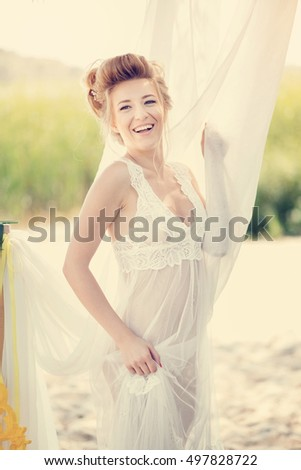 Beautiful blonde girl in peignoir posing wrapped in a white curtain