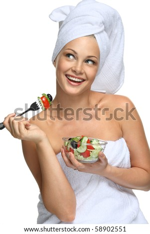 Beautiful blonde girl in towel eating fresh salad and smiling - stock photo