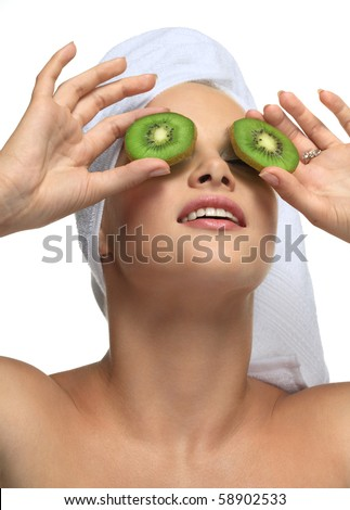 Beautiful blonde girl in towel with kiwi - on white - stock photo