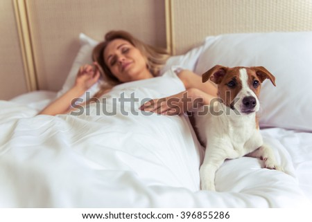 Beautiful blonde girl is sleeping in bed. Her cute dog is lying near and looking at camera - stock photo