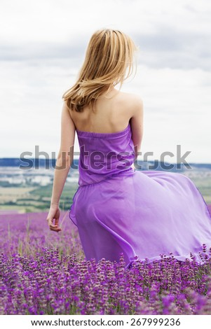 Beautiful blonde girl is wearing purple dress in fairy field of lavender. Summer time - stock photo