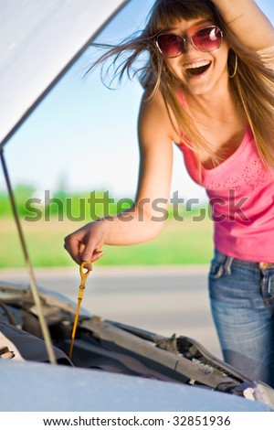 Beautiful blonde girl looking under the hood of the car - stock photo