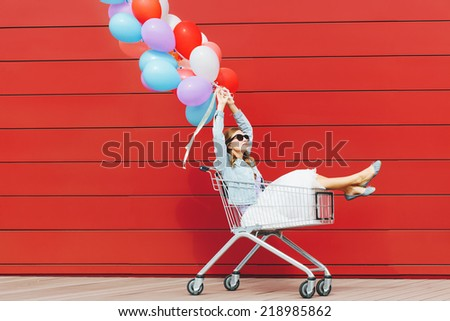 Beautiful blonde girl sitting in shopping cart, holding color balloons in both hand. Wearing sunglasses. Sunny day, outside - stock photo