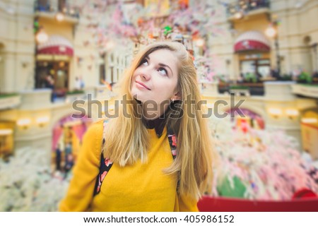 Beautiful blonde girl standing in the middle of shopping mall, thinking of shopping and buying new clothes and looking up, with trade center shopping area vibrant interior in the background - stock photo