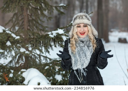 Beautiful blonde girl standing in winter forest near a tree and smiles surprise