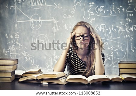 Beautiful blonde girl stressed by the study - stock photo