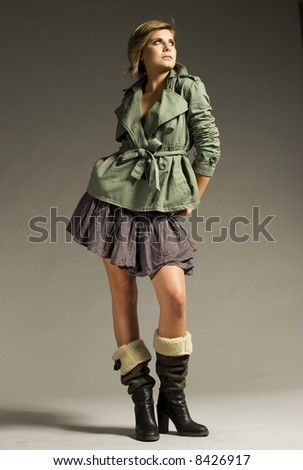 beautiful blonde girl wearing green coat and mini skirt on grey background - stock photo
