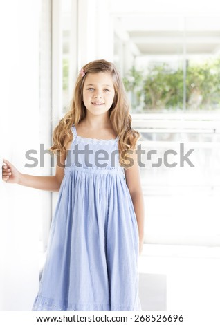 Beautiful blonde girl with blue eyes and light blue dress - stock photo