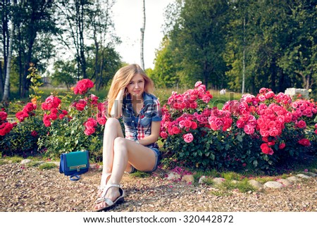 Beautiful blonde girl with flowers - stock photo