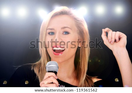Beautiful blonde girl with microphone singing on a concert with disco spotlights on the background