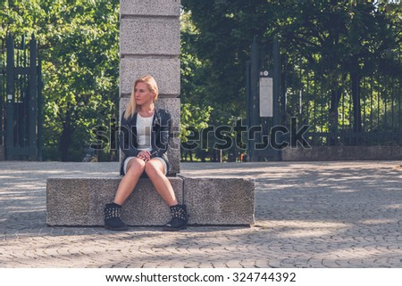 Beautiful blonde girl with white minidress and leather jacket posing in the city streets