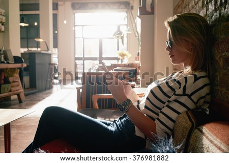 Beautiful blonde girl working at a coffee shop with a smart-phone. female freelancer connecting to internet via cellphone. flare light - stock photo
