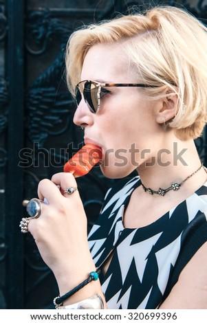 Beautiful blonde hipster female eating ice cream - stock photo