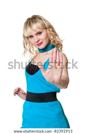 Beautiful blonde in a blue stop oncoming gesture poses in the studio on a white background - stock photo