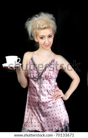 beautiful blonde in a nightgown with a cup in his hand on a black background - stock photo