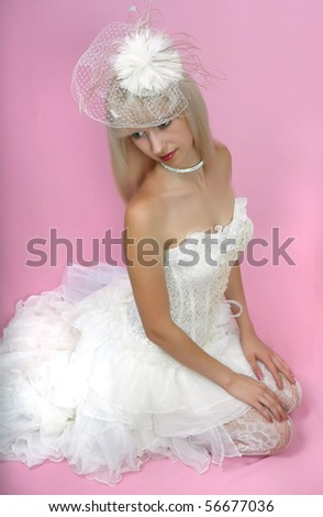 beautiful blonde in an extravagant hat and white dress - stock photo