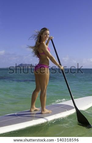 beautiful blonde in bikini on paddle board - stock photo