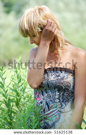 Beautiful blonde in sundress enjoys  unification with nature .