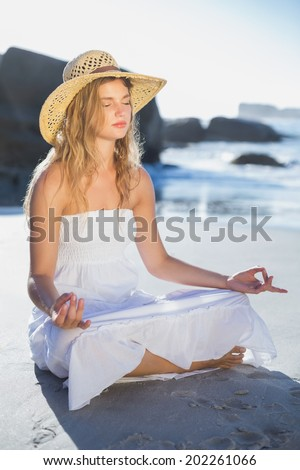 beautiful blonde in sundress sitting in lotus pose on the