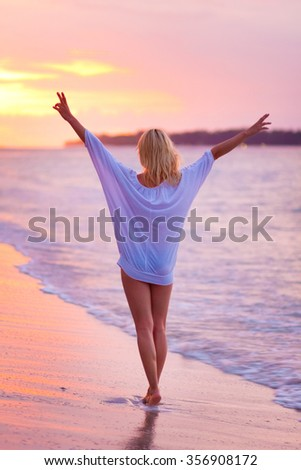 Beautiful blonde lady, arms rised in the sky, relaxing and enjoying vacations on the sandy tropical beach at sunset. - stock photo
